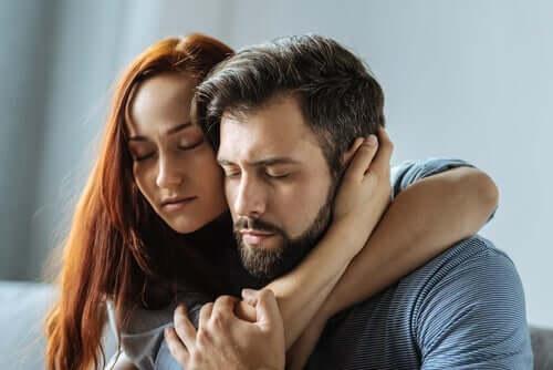 Et par sitter kinn mot kinn og omfavner hverandre med lukkede øyne.