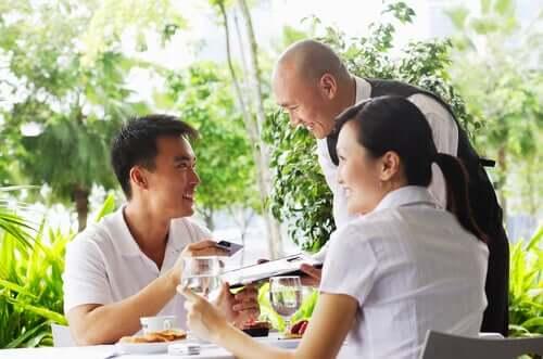 Et par i hvite klær sitter på en ute restaurant og gjør seg klar til å betale servitøren.