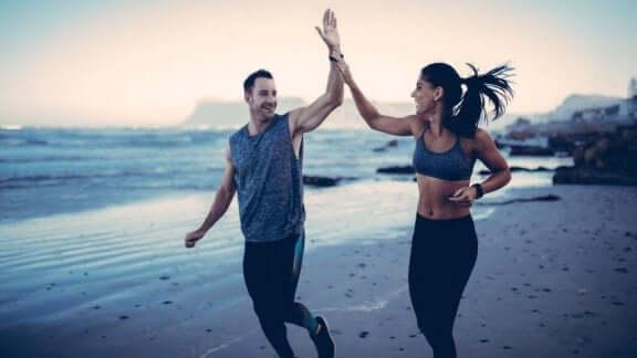 Et par løper på en sandstrand i solnedgang