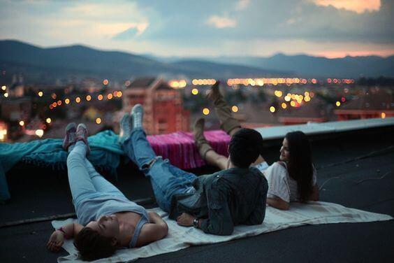 Venner ligger på en takterrasse og ser på solnedgangen.