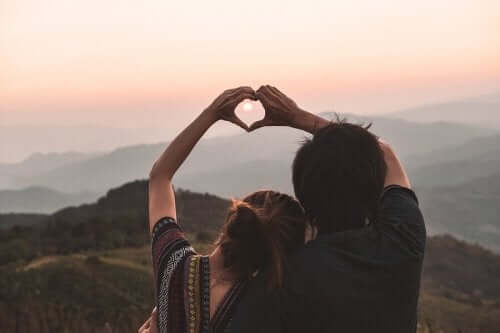 Mann og kvinner former hendene til et hjerte forran solnedgang.