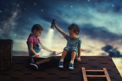 To barn som leser en bok på et hustak