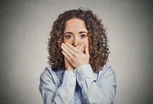 Kvinne som dekker munnen.