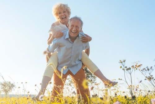 Eldre kvinne sitter på ryggen til en eldre mann