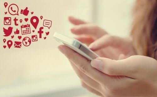 Bildet av en kvinnes hånd samtidig som hun tekster på en mobiltelefon