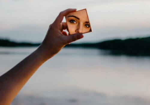 En kvinne som ser på seg selv i et lite speil