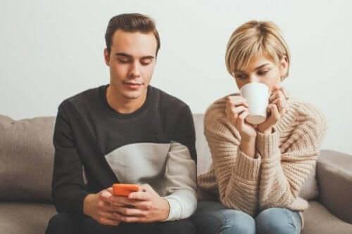 En kvinne som ser på kjærestens mobiltelefon mens hun drikker kaffe