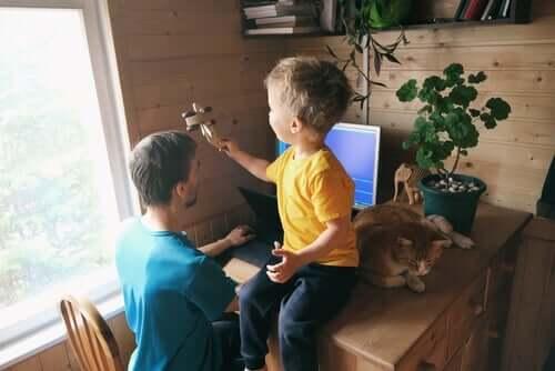 En far som arbeider og et barn med et leketøy
