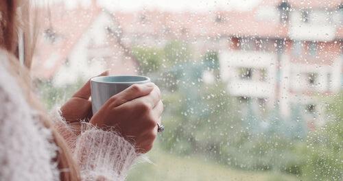 En kvinne med en kopp kaffe ved vinduet