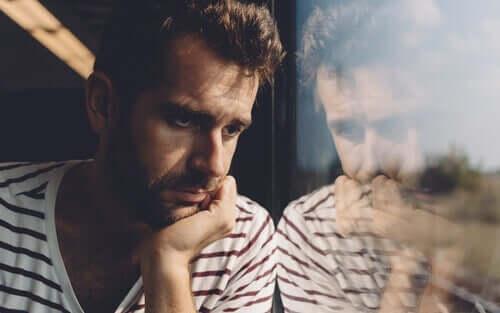 En bekymret mann ser ut av et vindu