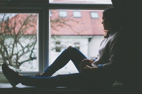 En kvinne sitter i vinduskarmen