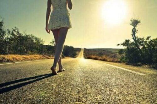 En kvinne som går barføtt midt på landeveien.
