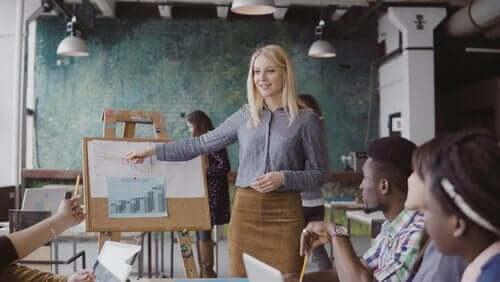 En kvinne som holder en presentasjon for en liten gruppe mennesker i en romslig bygning.