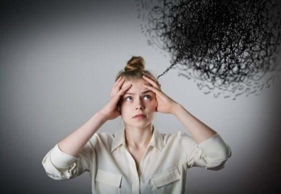 En kvinne som holder hendene mot hodet, stresset av den svarte skyen av negative tanker som henger over henne.