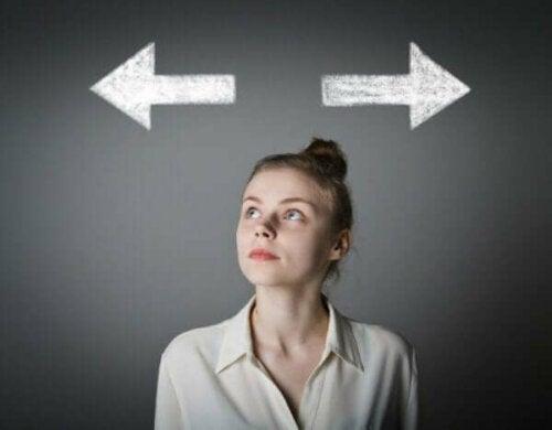 En kvinne som ser opp på to piler mens hun prøver å bestemme seg for hvilken vei hun skal gå, pilene symboliserer rasjonell valgteori.