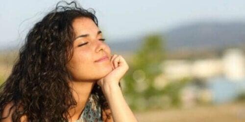 En kvinne som tar inn naturen med lukkede øyne.