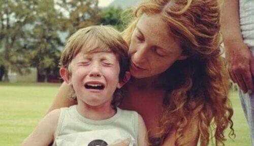 En mor som har blitt trent i førstehjelp for barn som hjelper et gråtende barn.