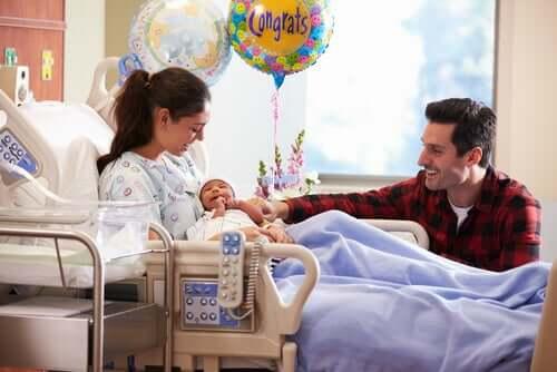 En ny mor som holder babyen sin på den venstre siden.