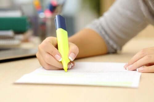En person som fremhever notater på et stykke papir.