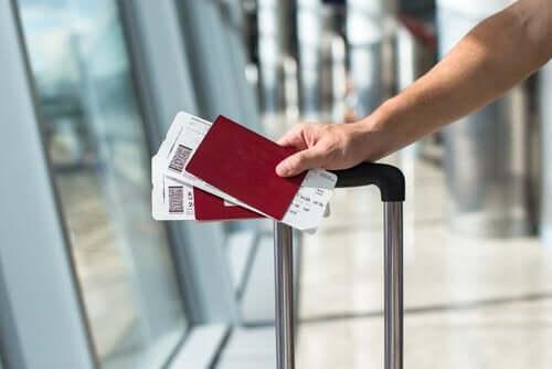 En person som går gjennom en flyplass med en koffert og to pass i hånden.