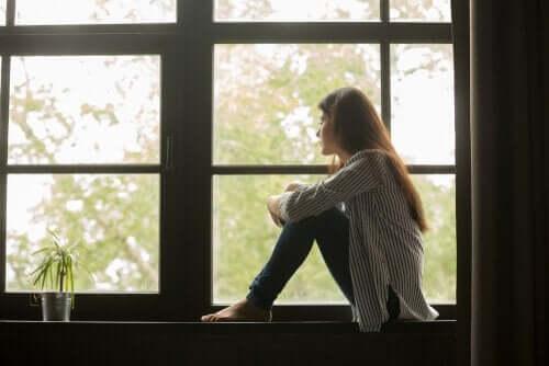 En trist kvinne som ser ut av vinduet og vurderer livet sitt.