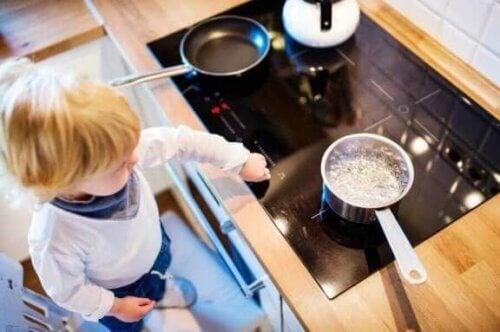 Et barn som berører en komfyrtopp med varme kjeler på.