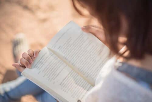 Kvinne sitter med en oppslått bok i fanget.