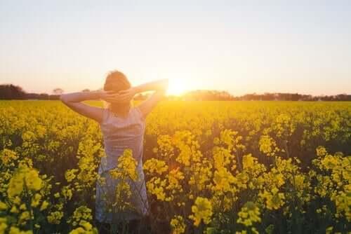 En kvinne står midt i en eng full av gule blomster i solnedgang.