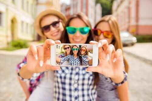 Tre smilende veninner med solbriller tar en selfie