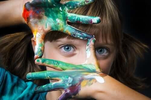 En jente med maling på hendene sine