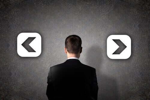 En mann som står foran to piler som peker motsatt vei