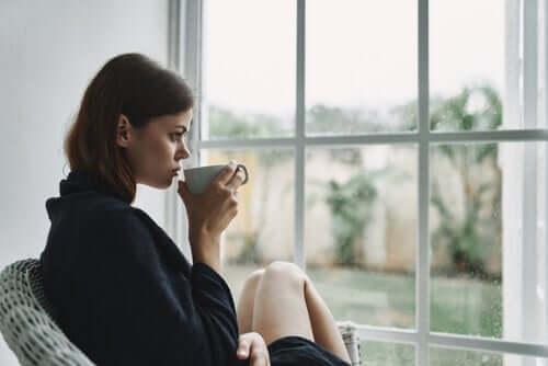 En kvinne drikker kaffe ved vinduet