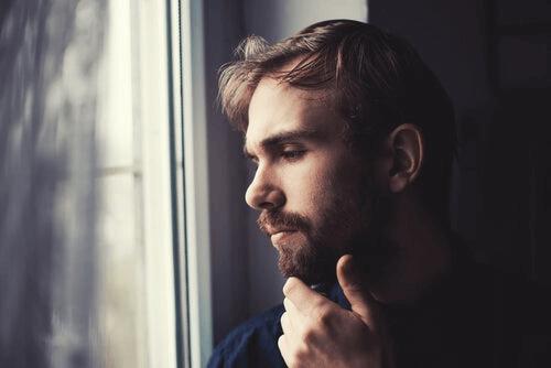 En mann sitter ved vinduet og tenker