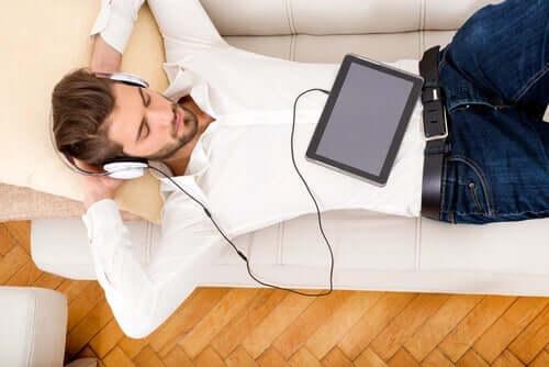 En mann ligger og lytter til musikk