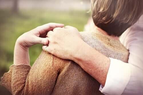 Vi ser ryggene til et par som omfavner hverandre