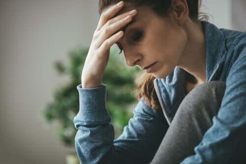 En tilsynelatende bekymret vinne sitter med hodet i hendene, kanskje er hun plaget av medavhengighet.