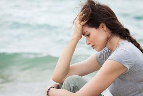 En bekymret kvinne som sitter nær sjøen.