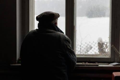 En gammel mann som ser ut av vinduet.