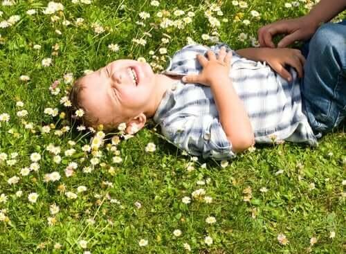 En gutt som ligger i en blomstereng som ler.