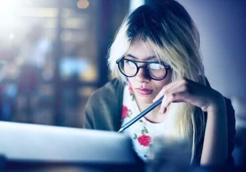 En kvinne som jobber og studerer ved en datamaskin.