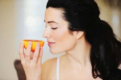 En kvinne som lukter på en appelsin.