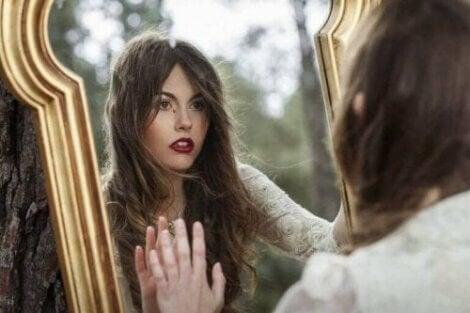 En kvinne som ser på refleksjonen sin i et speil.