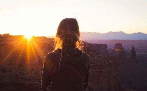 En kvinne som ser utover et landskap.