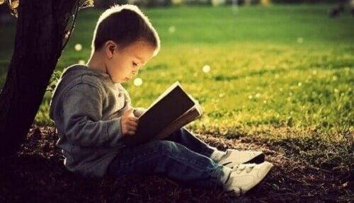 En liten gutt som leser en bok.