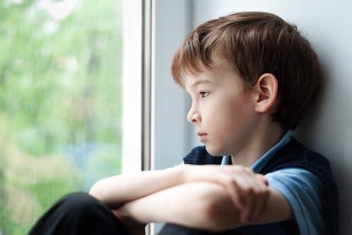 En trist liten gutt som ser ut av vinduet.