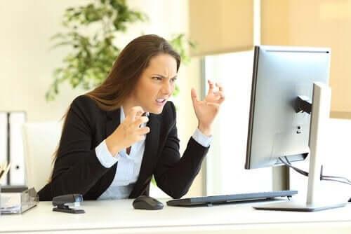 En utålmodig kvinne sitter på jobb.
