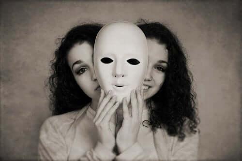 Et svart-hvitt bilde av ansiktet til to tilsynelatende identiske kvinner som gjemmer seg bak en maske.
