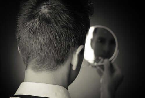Mann som ser seg i speilet.