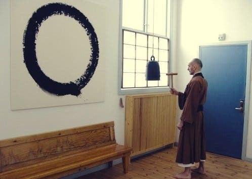En buddhistisk munk som stirrer på ensō-sirkelen på en vegg.