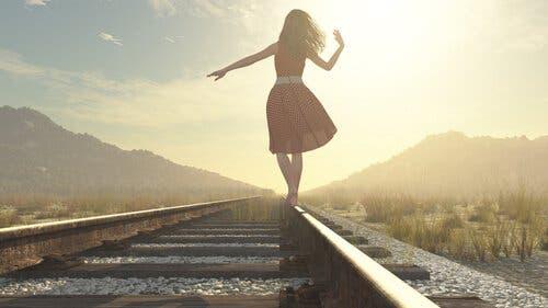 En kvinne som balanserer på en jernbane.